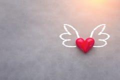 Aimez le concept avec l'objet rouge de coeur avec des ailes dessinant sur le Ba gris Photo stock