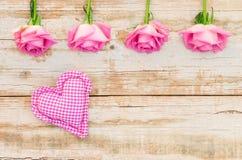 Aimez le fond avec le coeur rose et les roses sur le vieux bois blanc Photo libre de droits