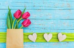 Aimez le fond avec les coeurs en bois rustiques et les fleurs rouges de tulipes sur le bois bleu-clair photo stock