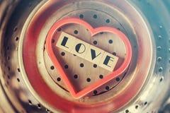 Aimez le message écrit avec les blocs en bois à l'intérieur d'un coeur rouge Photos stock