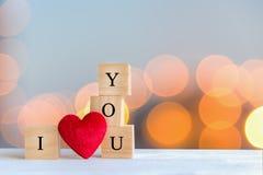 Aimez le message écrit dans les blocs en bois avec le coeur rouge, fond de bokeh Photos stock