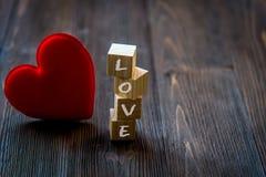 Aimez le message écrit dans les blocs en bois avec le coeur rouge, vieux fond en bois Image libre de droits