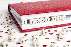 Aimez le message écrit dans les blocs en bois dans un carnet sur W blanc Photographie stock libre de droits