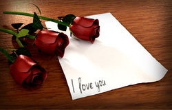 Aimez le message avec le papier de vintage et trois roses Photo libre de droits