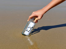 Aimez le message dans une bouteille sur la plage Photos stock