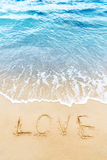 Aimez le mot écrit sur le sable de la plage Photographie stock