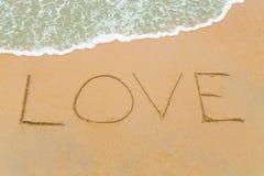 AIMEZ le mot dessiné sur la plage sablonneuse avec l'approche de vague Image libre de droits