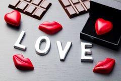 Aimez le mot, le coeur et les bonbons au chocolat formés par lèvres Photo libre de droits