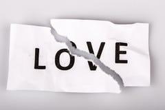 aimez le mot sur le papier déchiré - concept cassé d'amour Photo stock