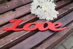 Aimez le mot sur un banc en bois avec le bouquet de fleur Images libres de droits