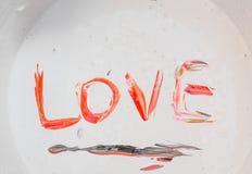Aimez, le rouge d'amour de mot de légende, noir dans la surface de couleur Images stock