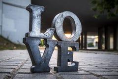Aimez le signe avec des lettres en métal dans une rue Image stock