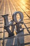 Aimez le signe avec des lettres en métal dans une rue Photos stock