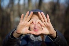 Aimez le signe de coeur de symbole des mains du ` s de fille photographie stock libre de droits