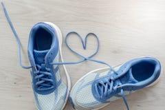 Aimez le signe, fin de foyer sélectif vers le haut des chaussures bleues de sport sur le gris Photos stock