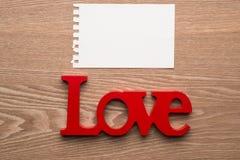 Aimez le symbole écrit dans la lettre en bois avec la carte de message Photo stock
