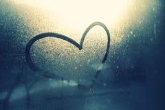 Aimez le symbole de coeur sur le fond humide et gelé de fenêtre Photographie stock libre de droits