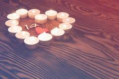 Aimez le symbole fait à partir de beaucoup de petites bougies sur le fond en bois Images stock