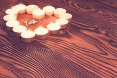 Aimez le symbole fait à partir de beaucoup de petites bougies sur le fond en bois Photo libre de droits