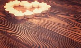 Aimez le symbole fait à partir de beaucoup de petites bougies sur le fond en bois Images libres de droits