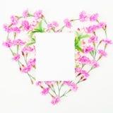 Aimez le symbole fait en fleurs et carte roses sur le fond blanc Configuration plate, vue supérieure Photo stock