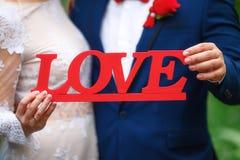 Aimez le texte dans des mains des jeunes mariés, épousant le concept Photographie stock