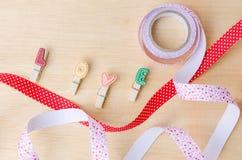 Aimez les agrafes avec les rubans mignons sur le fond en bois Images stock