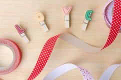 Aimez les agrafes avec les rubans mignons sur le fond en bois Photos libres de droits
