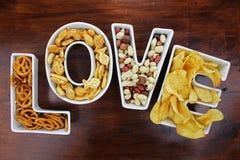 Aimez les casse-croûte de casse-croûte dans des cuvettes de lettre d'amour sur le bois foncé Photo libre de droits