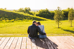 Aimez les couples étreignant sur un pilier dans la vue de dos de nature Photo stock
