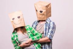 Aimez les couples couvrant leurs visages de sac de papier au-dessus du fond blanc Photographie stock