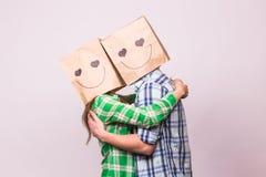 Aimez les couples couvrant leurs visages de sac de papier au-dessus du fond blanc Images stock