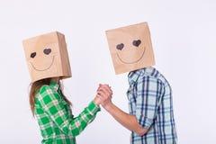 Aimez les couples couvrant leurs visages de sac de papier au-dessus du fond blanc Photos stock