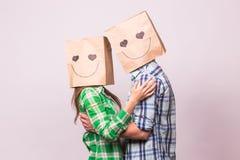 Aimez les couples couvrant leurs visages de sac de papier au-dessus du fond blanc Image stock
