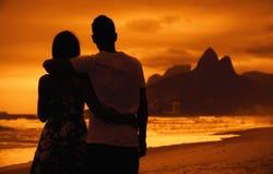 Aimez les couples dans des bras sur la plage au coucher du soleil chez Rio de Janeiro Photos stock