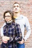 Aimez les couples embrassant le regard heureux contre le CCB de mur Image stock