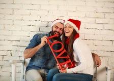 Aimez les couples heureux dans des chapeaux de Noël sur le mur blanc Photographie stock libre de droits