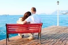 Aimez les couples se reposant sur le banc par l'embrassement de mer Image stock