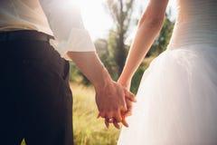 Aimez les couples tenant des mains dans le coucher du soleil de soirée Images libres de droits