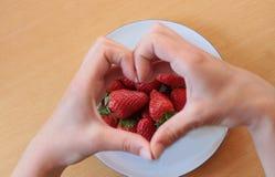 Aimez les fraises, mains formant un coeur au-dessus des fruits Photos stock