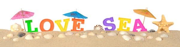 Aimez les lettres de mer sur un sable de plage sur un blanc Images stock
