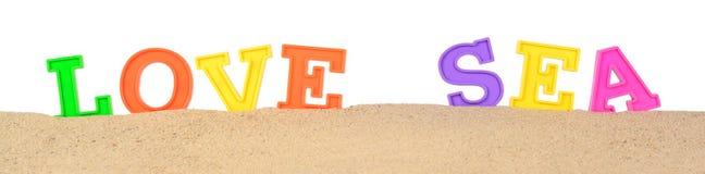 Aimez les lettres de mer sur un sable de plage sur un blanc Photo libre de droits