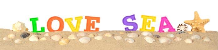 Aimez les lettres de mer sur un sable de plage sur un blanc Images libres de droits