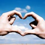 Aimez les mains de forme - coeur sur le champ jaune et le ciel bleu Photographie stock libre de droits
