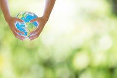 Aimez les mains jugeant de chaque côté le fond d'image de bokeh du monde meublé par la NASA photo libre de droits