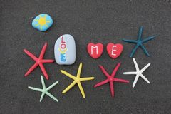 Aimez-moi message avec l'art de pierres et étoiles de mer au-dessus du sable noir Photos libres de droits