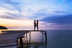 Aimez, silhouette des couples affectueux sur le pilier à la plage de coucher du soleil photos libres de droits
