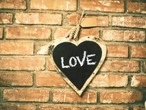 Aimez sur le panneau de craie de forme de coeur, avec le mur de briques de vintage Images stock