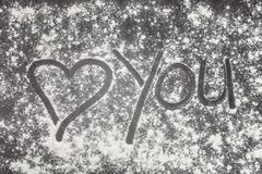 Aimez-vous avec le coeur peint avec le doigt dans le repas de blé sur une surface de fonctionnement grise Image stock