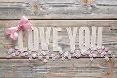 Aimez-vous - inscription et un arc rose sur le fond en bois Photo libre de droits